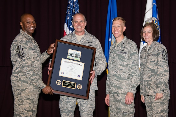 Chief Master Sgt. of the Air Force Kaleth O. Wright, presents Senior Master Sgt. Duane Caudill, 302nd Maintenance Group career advisor, with the 500,000th Community College of the Air Force degree, April 21, 2017, Maxwell Air Force Base, Ala. The Community College of the Air Force commandant, Lt. Col. Nathan J. Leap, and Chief Master Sgt. Vicki Robertson, 302 Airlift Wing Command Chief, also participated in the historic presentation. (US Air Force photo by Melanie Rodgers Cox)