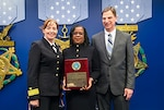 Mary McWilliams (center), DLA Land and Maritime electronics engineer, displays the Defense Standardization Program Award she received during a ceremony in Washington as she's flanked by DLA Land and Maritime Commander, RDML Michelle Skubic (left) and Michael Radecki, Land and Maritime's chief of electronics components on the right. (U.S. Army photo by Sgt. Alicia Brand)
