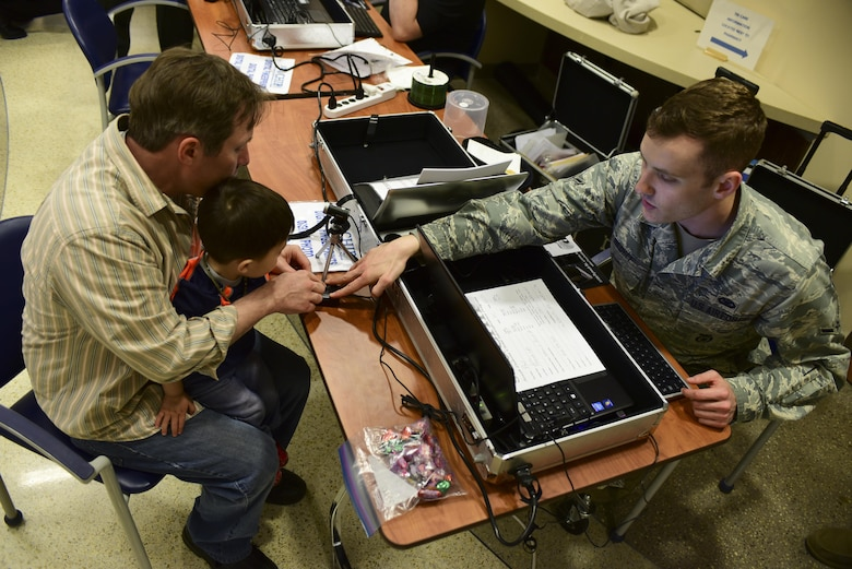 Steven Romehildt helps his son, Paul, scan his fingerprint during the 2017 Children's Fair inside the 28th Medical Group at Ellsworth Air Force Base, S.D., April 20, 2017. Parents received a child-identification kit to help law enforcement find their child if they were to become lost. (U.S. Air Force photo by Airman 1st Class Randahl J. Jenson)