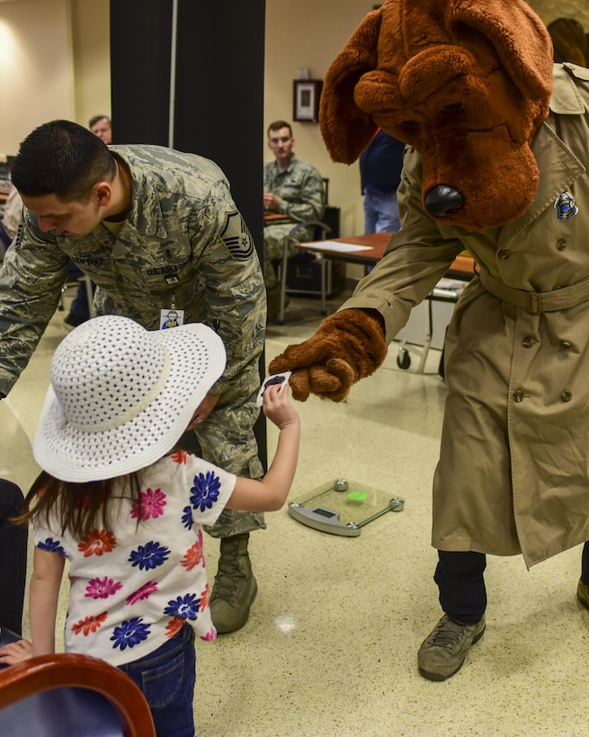 McGruff the Crime Dog passes out stickers during the 2017 Children's Fair inside the 28th Medical Group at Ellsworth Air Force Base, S.D., April 20, 2017. Both McGruff the Crime Dog and Sparky the Fire Dog participated in the event, supporting Child Abuse Prevention Awareness Month by handing out stickers, hugs and high-fives. (U.S. Air Force photo by Airman 1st Class Randahl J. Jenson)