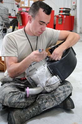 Senior Airman Matthew Gadziala, 924th Fighter Group electrical and environmental specialist, replaces the inlet and outlet ducts on a pre-cooler prior to re-installing it on a A-10 Thunderbolt II at Davis-Monthan Air Force Base, Ariz. Gadziala joined the Air Force for a change of pace however he is still going to school to be a doctor, his ultimate goal. (U.S. Air Force photo by Tech. Sgt. Courtney Richardson)