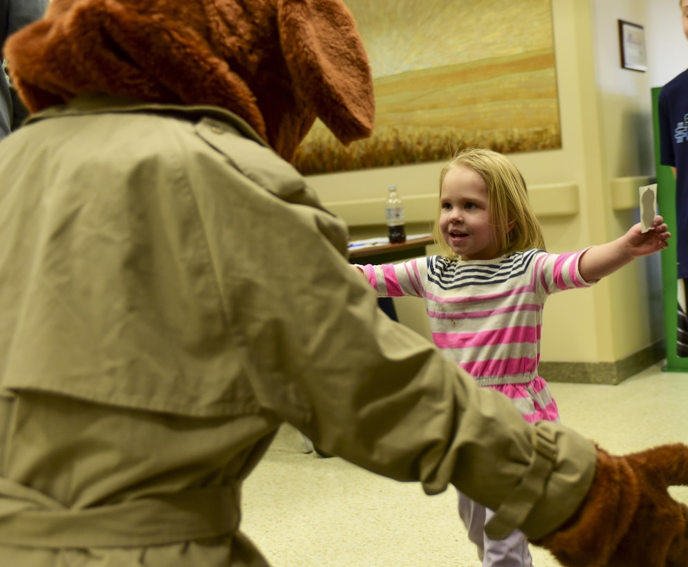Alexa Henriksen runs to give McGruff the Crime Dog a hug during the 2017 Children's Fair inside the 28th Medical Group at Ellsworth Air Force Base, S.D., April 20, 2017. McGruff the Crime Dog and Sparky the Fire Dog participated in the Children's Fair to raise awareness for Child Abuse Prevention Awareness Month. (U.S. Air Force photo by Airman 1st Class Randahl J. Jenson)