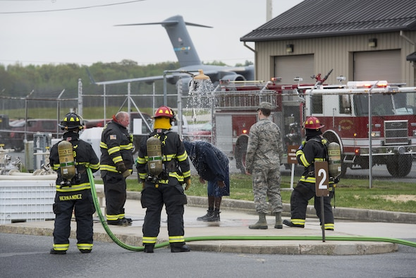 Firefighters assigned to the 436th Civil Engineer Squadron operate an emergency shower to remove simulated Jet-A fuel from a person who feigned full-body exposure during a fuel spill exercise April 20, 2017, at Dover Air Force Base, Del. After showering, members exposed to dermal contact with jet fuel or other hazardous materials require immediate medical evaluation and treatment. (U.S. Air Force photo by Senior Airman Aaron J. Jenne)