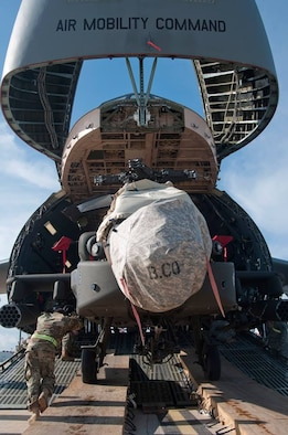 An AH-64 Apache helicopter is loaded onto a Team Dover C-5M Super Galaxy airlifter March 26, 2017, at Naval Station Rota, Spain. This was part of a U.S. Transportation Command Multimodal operation that deployment swapped two Army Aviation Brigades in and out of Afghanistan. (Courtesy photo)