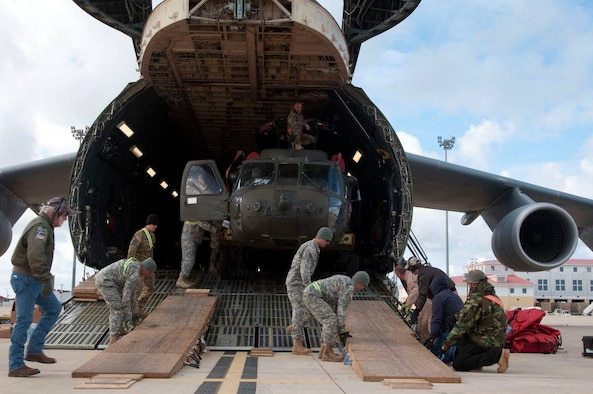 An HH-60 Black Hawk helicopter is unloaded from a Team Dover C-5M Super Galaxy airlifter March 26, 2017, at Naval Station Rota, Spain. The combined active duty and Reserve force used four Dover C-5Ms, flying more than 450 hours to transport 82 helicopters, 46 passengers, and support equipment totaling 2.6 million pounds over the duration of the mission. (Courtesy photo)