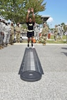 Pfc. Kenya Walker, assigned to the 302d Inland Cargo Transportation Company, demonstrates how to properly perform the standing long jump during the Army Reserve 109th Birthday Celebration on Joint Base-Langley, Virginia 21 April 2017.  The standing long jump is one of four battery exercises on the Occupational Physical Assessment Test (OPAT) used to assess an individual's physical capabilities to engage demanding Army tasks.