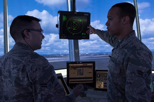 A trainer and trainee interact during a lesson of radar monitoring at the Air Traffic Control Tower Apr. 18, 2017, Fairchild Air Force Base, Washington. All ATC Airmen are trained in tower and radar operations, yet require up to a year of additional on the job experience before they can man a station solo. (U.S. Air Force photo/Airman 1st Class Ryan Lackey)