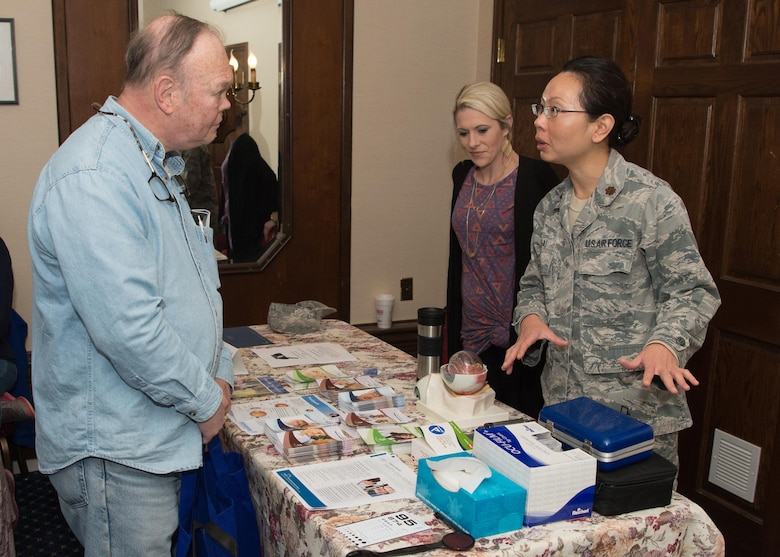 Maj. Marilyn Lai, 66th Medical Squadron optometrist, talks with Douglas Miller during Military Retiree Appreciation Day at the Minuteman Commons April 21, while Abigail Tarbox, 66 MDS optometry technician, listens. This year's event began with an Information Services session followed by a presentation by the Fraud Watch Network. (U.S. Air Force photo by Jerry Saslav)