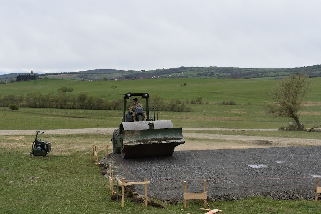 Sgt. Jesse Ellis, a heavy equipment operator of 390th Engineer Company, 844th Engineer Battalion out of Chattanooga, TN, levels and grades the base layer for the multipurpose building with a roller on 19 April 2017 at Cincu Training Area, Romania. This establishes a solid footing for the concrete pad that will be the floor of the building. The project is a part of Resolute Castle 17, an exercise which strengthens the NATO alliance. (US Army photo by Capt. Colin J. Cutler, 926th Engineer Brigade)
