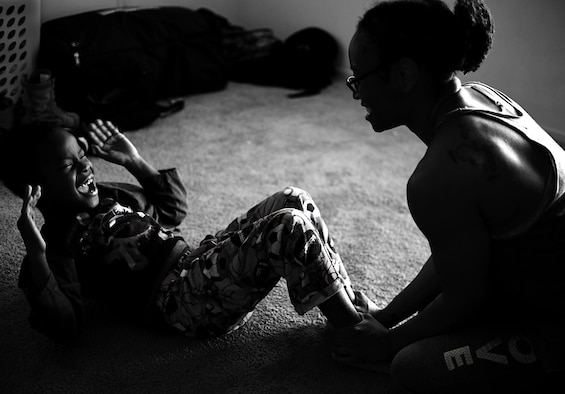 Semaj, 432nd Aircraft Maintenance Squadron supply craftsman, assists her son Jamel, 6, with situps April 2, 2017, at their home in Las Vegas. Semaj is a nationally qualified amateur bodybuilder competing in the figure category. (U.S. Air Force photo/Senior Airman Christian Clausen)