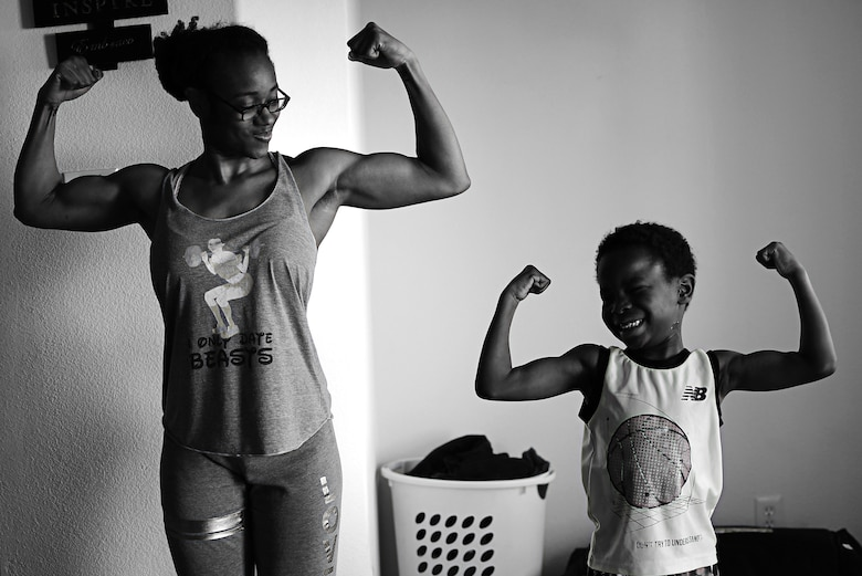 Semaj, 432nd Aircraft Maintenance Squadron supply craftsman, and her son Jamel, 6, strike a muscle pose April 2, 2017, at their home in Las Vegas. Semaj recently took second place in the 2017 National Physique Committee Southern Championships in the figure category. She is now a nationally qualified amateur bodybuilder seeking her professional card. (U.S. Air Force photo/Senior Airman Christian Clausen)