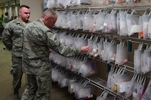 Senior Airman Sean Rourke, 460th Medical Operations Squadron pharmacy technician, discusses new techniques of organizing the Buckley Community's medication with Brig. Gen. James Burks, Director, Manpower, Personnel, and Resources Corps Chief, Medical Service Corps, April 25, 2017, on Buckley Air Force Base, Colo. Burks toured the medical facilities on base and was briefed the status of each unit. (U.S. Air Force photo by Airman Jacob Deatherage/Released)