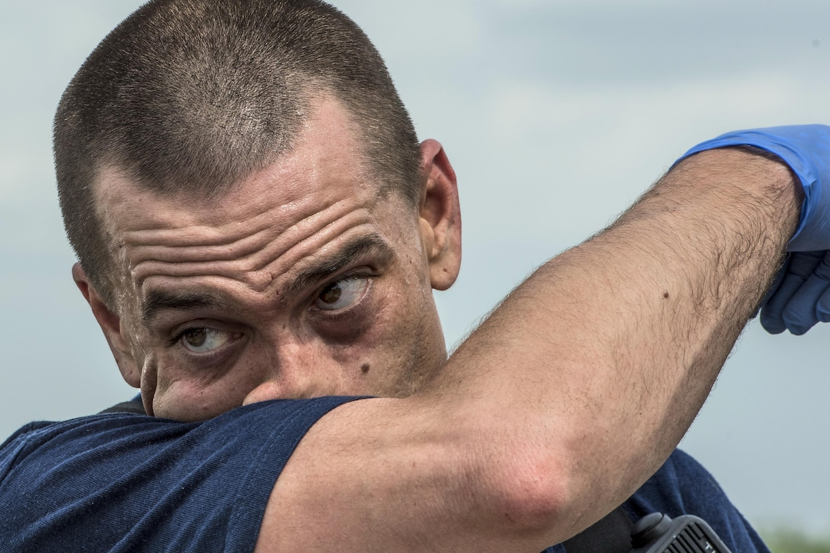 An airman wipes sweat from his face after tending to simulated injured patients.