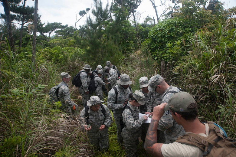 U.S. Air Force Airmen assigned to the 18th Medical Group and 18th Operations Support Squadron navigate a jungle as part of an exercise during the Preventative Aerospace Medicine Convention April 21, 2017, at Kadena Air Base, Japan. Members of the 18th OSS survival, evasion, resistance and escape flight assist the PAMACON by providing training on how to safely navigate with maps and compasses.  (U.S. Air Force photo by Airman 1st Class Quay Drawdy)