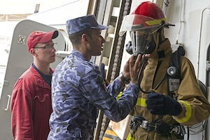 Damage Controlman 2nd Class Cody Osgood observes as Egyptian Navy Sailors put on firefighting equipment during Damage Control (DC) Olympics onboard guided-missile destroyer USS Truxtun (DDG 103) as part of Exercise Eagle Salute 17. Eagle Salute/Eagle Response 17 is a multilateral exercise with Egypt, Saudi Arabia and United Arab Emirates to enhance mutual capabilities in maritime security operations. Truxtun is deployed to the U.S. 5th Fleet area of operations in support of maritime security operations designed to reassure allies and partners and preserve the freedom of navigation and the free flow of commerce in the region.