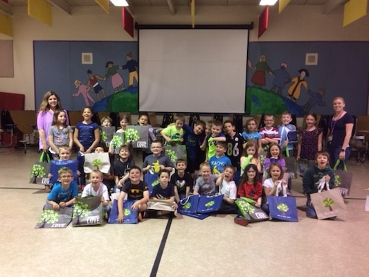 Students from Fairview Elementary pose with their new reusable bags after an Earth Day event hosted by Sarah Moor, environmental protection specialist with DLA Installation Support for Distribution.