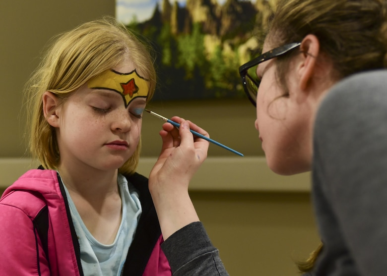 Jennifer Strickland, the daughter of 1st Lt. Daniel Strickland, the 28th Medical Readiness flight commander assigned to the 28th Medical Squadron, has her face painted by Jeena Simunek during the 2017 Children's Fair inside the 28th Medical Group at Ellsworth Air Force Base, S.D., April 20, 2017. The Children's Fair raises awareness for child abuse prevention, and provides parents with on and off-base family-centered resources. (U.S. Air Force photo by Airman 1st Class Randahl J. Jenson)