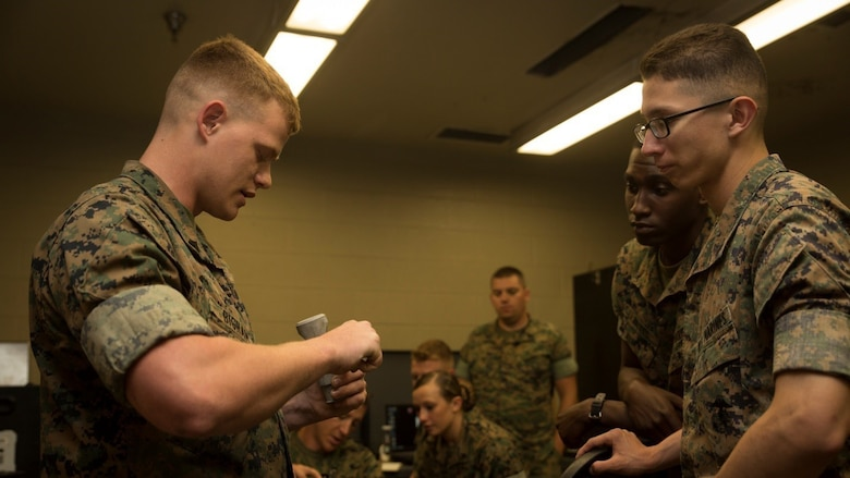 Cpl. Christopher A. Bigham (left), an instructor for the 3-D Printing Training Course and a machine shop noncommissioned officer with General Support Maintenance Company, 2nd Maintenance Battalion, Combat Logistics Regiment 25, 2nd Marine Logistics Group, demonstrates how to use calipers during a reverse engineering class at Marine Corps Base Camp Lejeune, North Carolina, April 20, 2017. Marines from various sections of Special Purpose Marine Air-Ground Task Force - Southern Command attended the two-day training hosted by GSM Co., 2nd Maint. Bn., CLR 25, 2nd MLG, in order to gain hands-on experience with 3-D printers and receive instruction in computer-aided design, file creation and manufacturing.