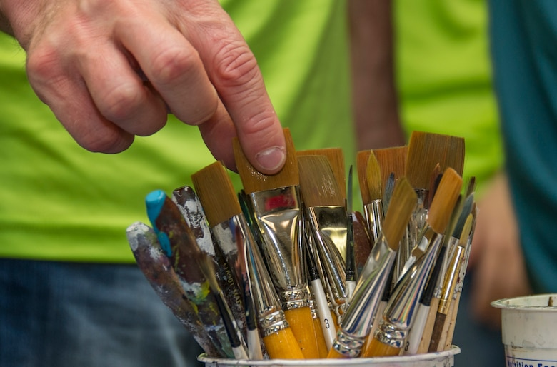 SCHRIEVER AIR FORCE BASE, Colo. -- Maj. Nathan Case, 310th Operations Support Squadron, selects a brush to start his first project during an art therapy class hosted by Kim le Nguyen at the Bemis School of Art in Colorado Springs on Friday, Apr. 21st, 2017. Nguyen teaches a Military Artistic Healing program at the Colorado Springs Fine Arts Center, using all forms of art to encourage healing among military members and their families.  (U.S. Air Force photo/Senior Airman Laura Turner)
