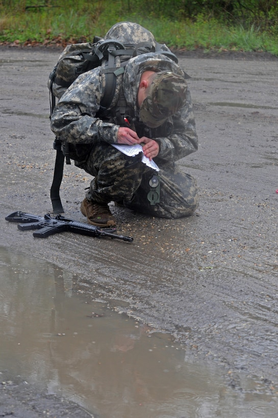 U.S. Army Reserve Sgt. Kevin Warren, 316th Mobility Augmentation Company, 844th Engineer Battalion , 926th Engineer Brigade, 412th Theater Engineer Command, is reflected in a pool of water as he double checks his map's point during the Combined Best Warrior Competition Land Navigation event on Joint Base McGuire-Dix-Lakehurst, N.J. April 4, 2017. Contestants hopefully take the title of Best Noncommissioned Officer or Best Soldier and move on to represent the 412th Theater Engineer Command,  416th Theater Engineer Command and 76th Operational Response at the USARC Best Warrior Competition. (U.S. Army Reserve Photo by Sgt. 1st Class Clinton Wood)