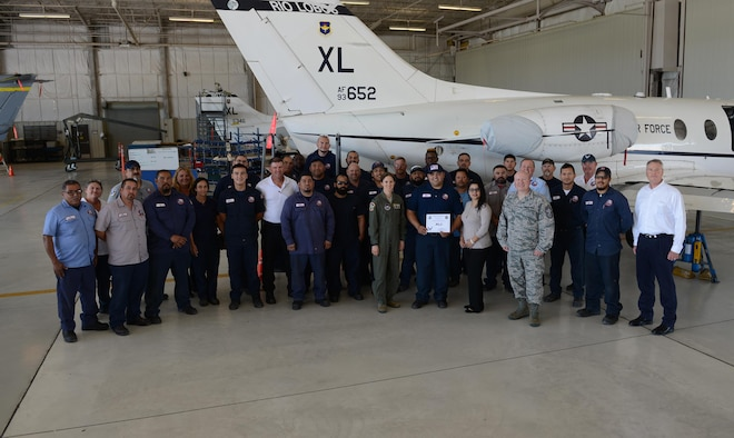 "Israel Levrie, 47th Maintenance Directorate aircraft mechanic (center), accepts the ""XLer of the Week"" award from Col. Michelle Pryor, 47th Flying Training Wing vice commander (left), and Chief Master Sgt. Eric Hall, 47th Medical Group superintendent (right), on Laughlin Air Force Base, Texas, April 20, 2017. The XLer is a weekly award chosen by wing leadership and is presented to those who consistently make outstanding contributions to their unit and Laughlin. (U.S. Air Force photo/Airman 1st Class Benjamin N. Valmoja)"