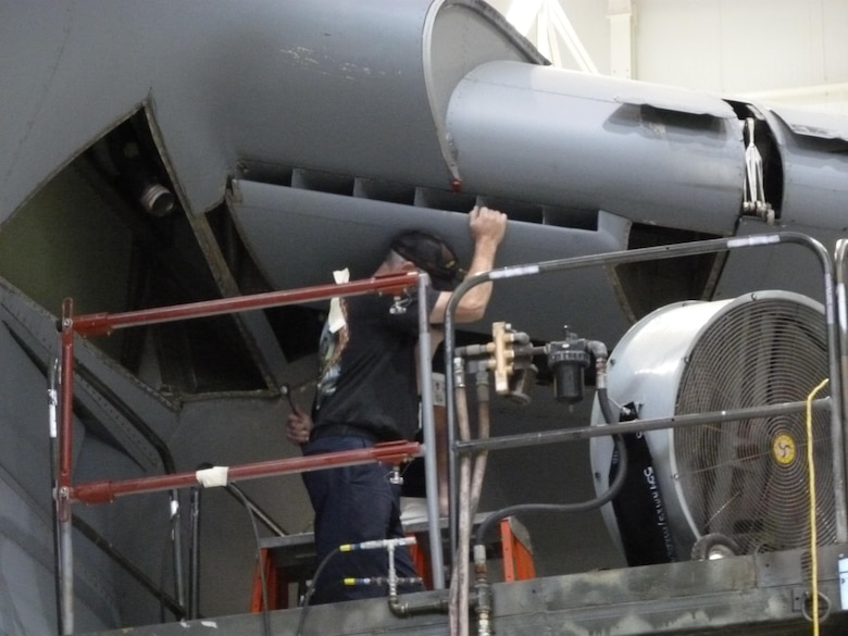 A maintainer removes an air inlet on the underside of the wing of a C-5M Super Galaxy Transport Aircraft during a periodic maintenance cycle. The Air Force Research Laboratory's Advanced Power Technology Office is in the process of testing a new, lightweight composite RAM Air Inlet system that is intended to replace legacy air inlets, mitigating corrosion issues while providing a lightweight, cost-effective solution to help maintain the fleet. (U.S. Air Force courtesy photo)