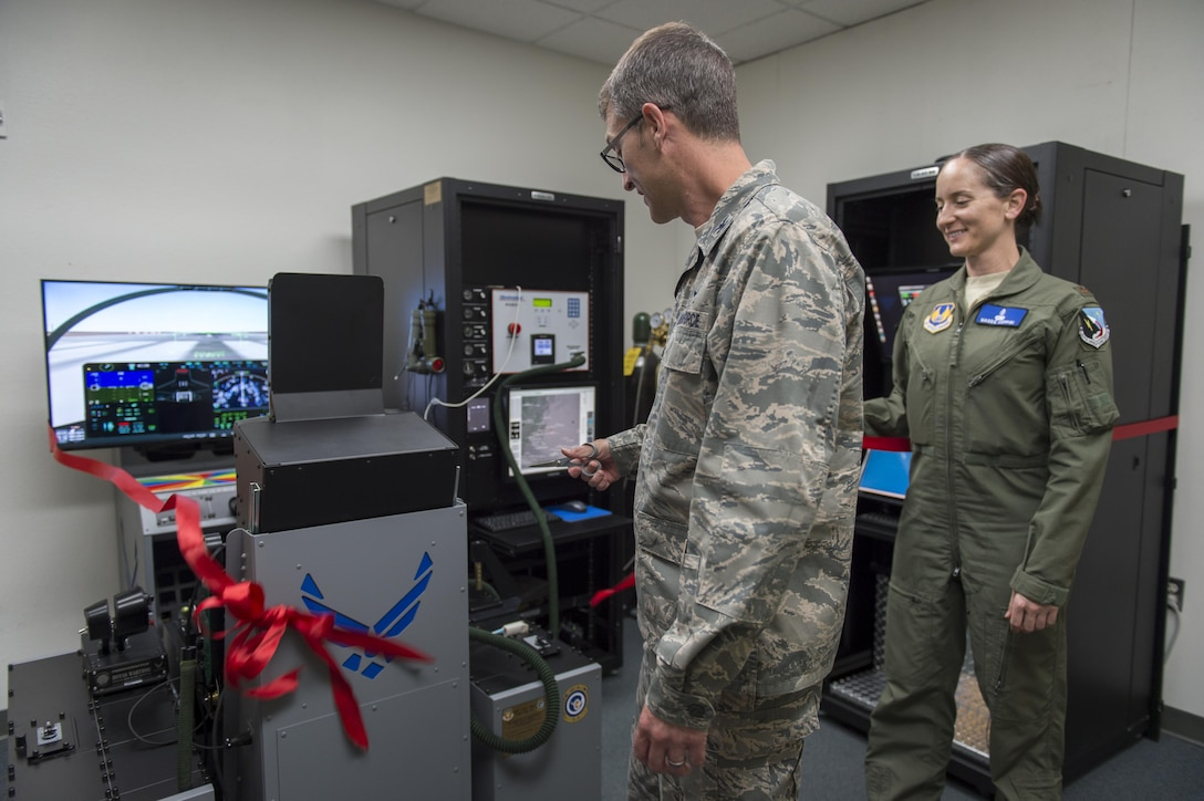 Maj. Maggie Coppini, 412th Medical Group aerospace physiologist, watches Col. Scott Cain, 412th Operations Group commander, cut the ceremonial ribbon signifying the introduction of a new hypoxia trainer located at the 412th Operations Support Squadron's Aircrew Flight Equipment Aircrew Operations building April 20. (U.S. Air Force photo by Kyle Larson)