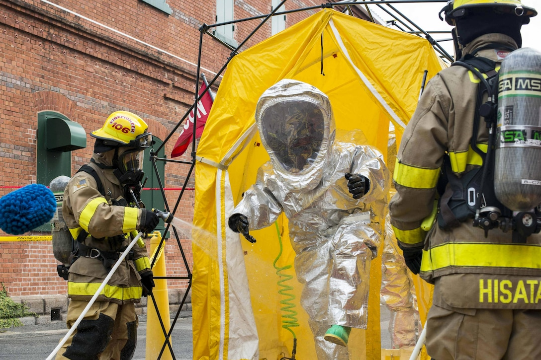 Sailors decontaminate a fire proximity suit during a preparedness exercise.