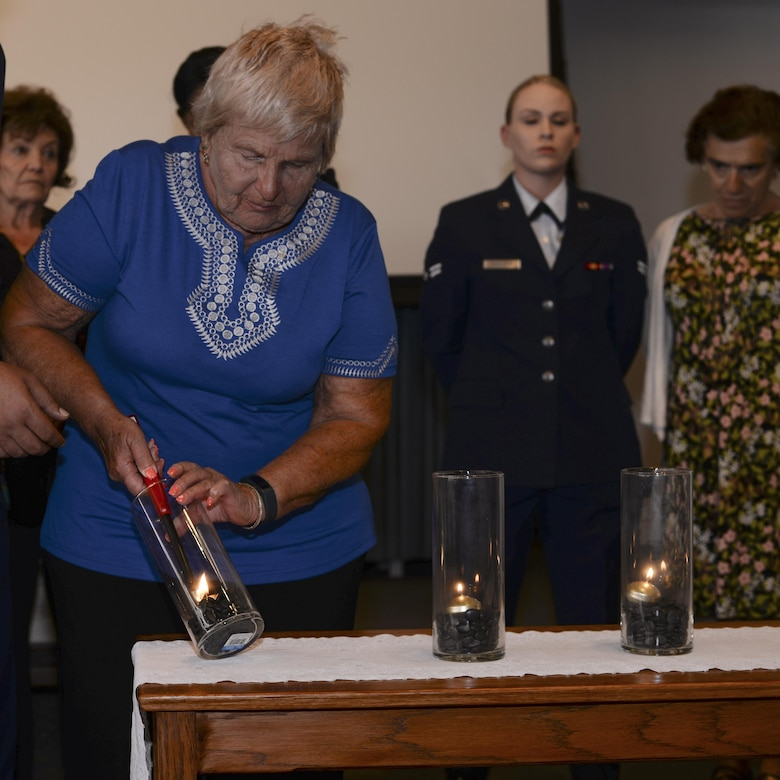 Wanda Wolosky, Holocaust survivor, lights a candle during a Holocaust remembrance ceremony at Davis-Monthan Air Force Base, Ariz., April 24, 2017. The ceremony was held to honor the 6 million Jews and millions of others that lost their lives during the Holocaust. (U.S. Air Force photo by Airman 1st Class Giovanni Sims)