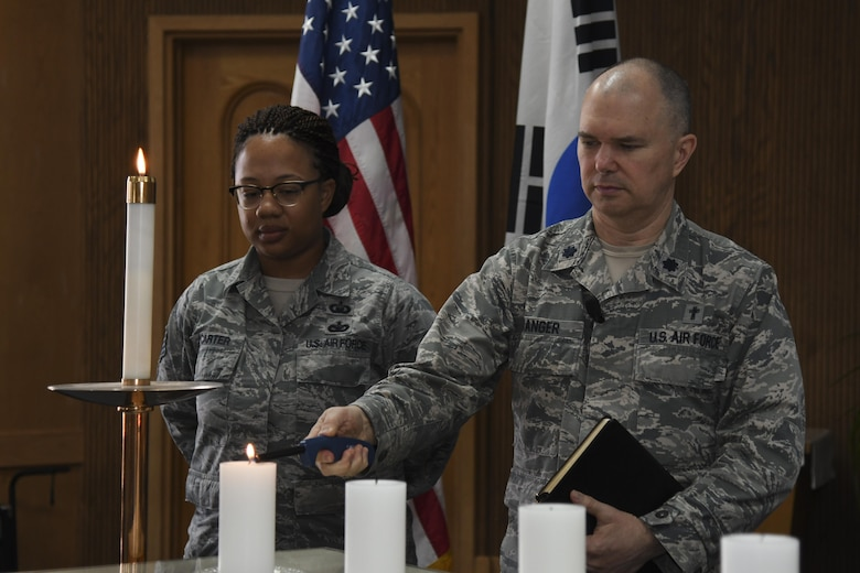 U.S. Air Force Chap. (Lt. Col.) Jeffery Granger, 51st Fighter Wing chaplain, lights a candle during a Holocaust Remembrance Day ceremony at Osan Air Base, Republic of Korea, April 25, 2017. Six candles were lit at the end of the ceremony to represent the estimated 6 million Jews executed during the Holocaust. (U.S. Air Force photo by Airman 1st Class Gwendalyn Smith)