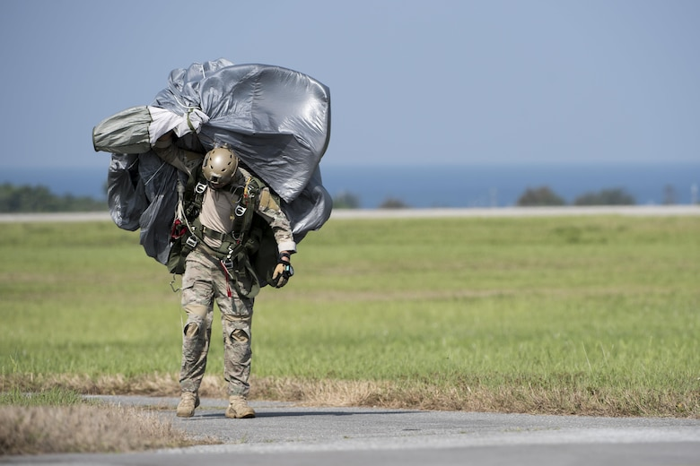 A U.S. Air Force Airman carries parachute gear after conducting a high altitude, low opening jump April 24, 2017, at Kadena Air Base, Japan. Soldiers and Airmen rely on properly prepared parachutes to safely land and conduct operations. (U.S. Air Force photo by Senior Airman Omari Bernard)