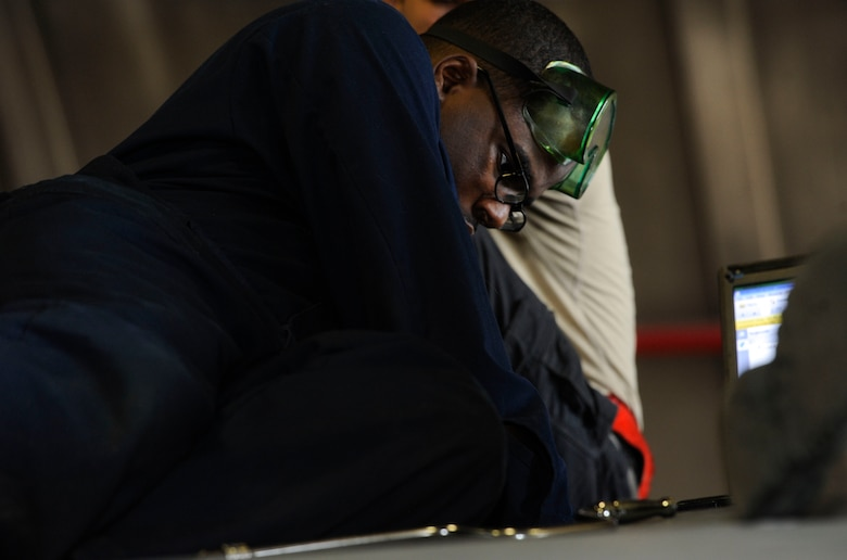 U.S. Air Force Airman 1st Class Tychaun Kingston, 44th Aircraft Maintenance Unit crew chief, performs maintenance on an aileron switching valve April 24, 2017, at Kadena Air Base, Japan. The aileron switching valve directs hydraulic fluid to the ailerons, providing pressure to the rudders. (U.S. Air Force photo by Senior Airman Lynette M. Rolen)