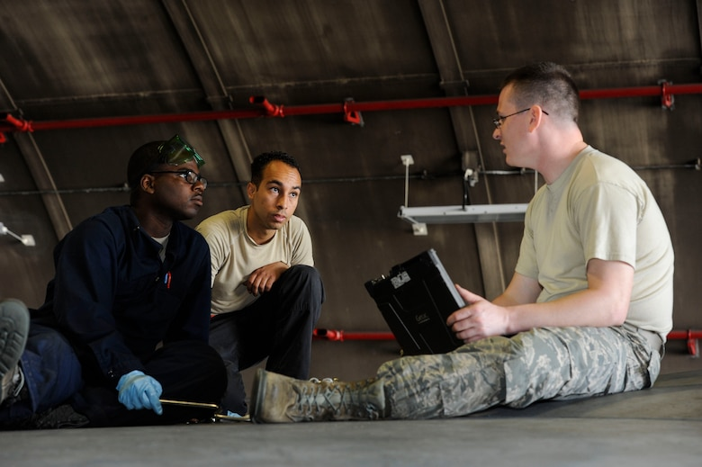 U.S. Air Force Tech. Sgt. Timothy Peppler, 372nd Training Squadron, Detachment 15, F-15 Eagle aircraft maintenance instructor, Senior Airman Devon Moore, 67th Aircraft Maintenance Unit crew chief, and Airman 1st Class Tychaun Kingston, 44th AMU crew chief, review training content April 24, 2017, at Kadena Air Base, Japan. After Airmen complete each training task, the instructor reviews their actions and provides feedback. (U.S. Air Force photo by Senior Airman Lynette M. Rolen)