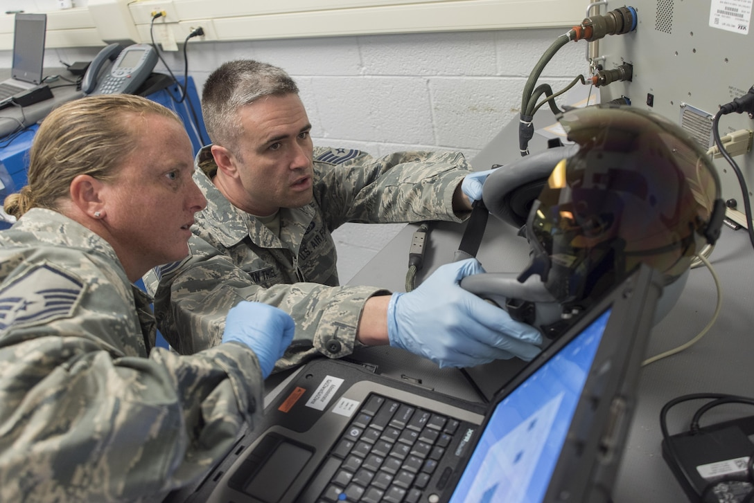 Master Sgt. Brandi Bray and Tech. Sgt. Eduard Van Thiel, 339th Flight Test Squadron aircrew flight equipment, operate a head-mounted display test system April 26, 2017, at Robins Air Force Base, Georgia. Aircrew flight equipment Airmen with the 339th FLTS are responsible for performing inspections, maintenance and adjustments to F-15 and C-5 flight and safety equipment. (U.S. Air Force photo by Jamal D. Sutter)