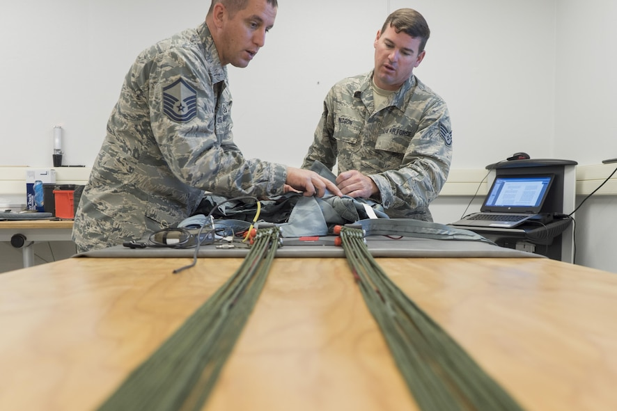 Master Sgt. Kevin Spano, left, and Staff Sgt. Scott Watson, 339th Flight Test Squadron aircrew flight equipment, conduct quality assurance to a parachute harness April 26, 2017, at Robins Air Force Base, Georgia. Aircrew flight equipment specialists ensure all flight and safety equipment are operational and able to be fully utilized during operations and emergency situations. (U.S. Air Force photo by Jamal D. Sutter)