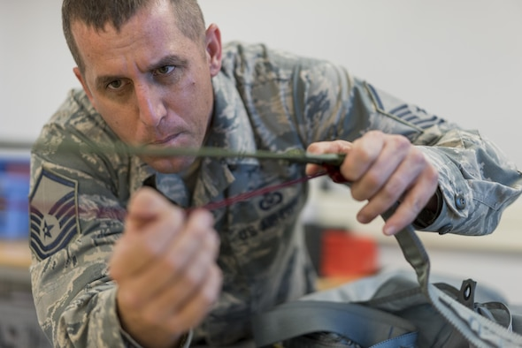 Master Sgt. Kevin Spano, 339th Flight Test Squadron aircrew flight equipment NCO in charge, inspects parachute lines April 26, 2017, at Robins Air Force Base, Georgia. One thing to look for when inspecting parachute lines is to ensure no lines are tangled together. (U.S. Air Force photo by Jamal D. Sutter)