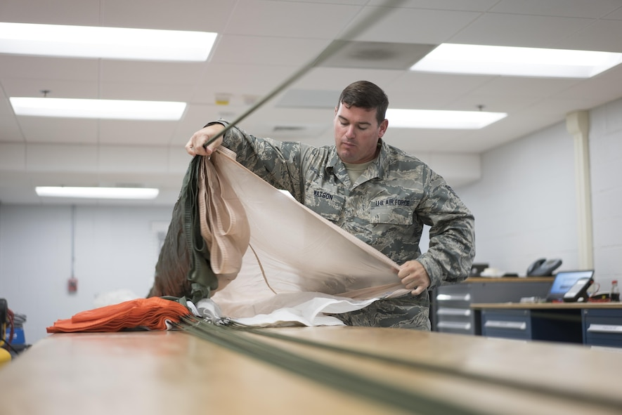 Staff Sgt. Scott Watson, 339th Flight Test Squadron aircrew flight equipment technician, inspects a parachute April 26, 2017, at Robins Air Force Base, Georgia. Aircrew flight equipment Airmen with the 339th FLTS are responsible for performing inspections, maintenance and adjustments to F-15 and C-5 flight and safety equipment. (U.S. Air Force photo by Jamal D. Sutter)