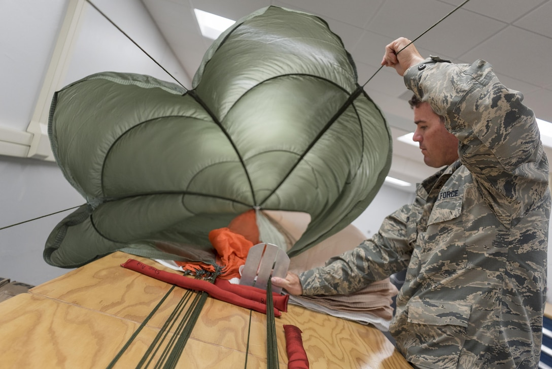 Staff Sgt. Scott Watson, 339th Flight Test Squadron aircrew flight equipment technician, inspects a parachute April 26, 2017, at Robins Air Force Base, Georgia. Aircrew flight equipment specialists ensure all flight and safety equipment are operational and able to be fully utilized during operations and emergency situations. (U.S. Air Force photo by Jamal D. Sutter)
