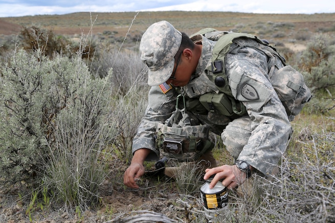 Army 1st Lt. Josiah Duka collects ants during a survival, evasion, resistance, and escape class at the Yakima Training Center, Yakima, Wash., April 25, 2017. Soldiers focused on the five basic needs for desert conditions. Army photo by Sgt. Kalie Jones