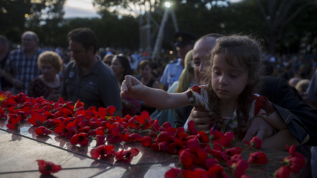 Citizens of Australia place Red Poppy flowers on an ANZAC memorial, in Darwin, Australia, April 25, 2017. Australia and New Zealand celebrate ANZAC Day as a way to thank all who has served and to honor all who gave the greatest sacrifice.