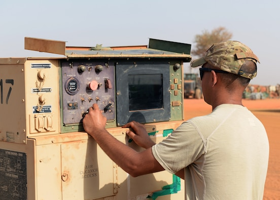 Staff Sgt. Eric Erquiza, 768th Expeditionary Air Base Squadron NCO in charge of Power Production, checks the settings on a generator at Nigerien Air Base 101, Niger, April 1, 2017. Periodic maintenance on the generators helps to cut down on wear and tear, and keeps them operating efficiently. (U.S. Air Force photo by Senior Airman Jimmie D. Pike)
