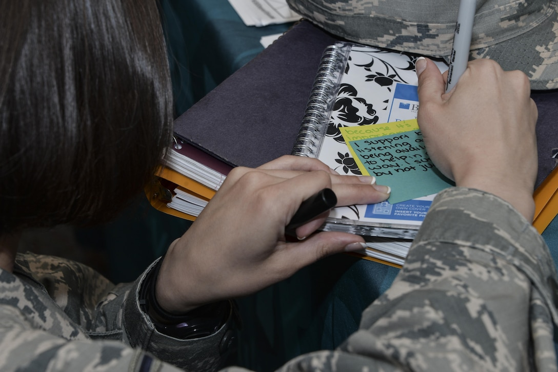 Airman Amanda, 32nd Intelligence Squadron, writes a message to sexual assault survivors on a sticky note as part the Stick with Survivors project April 13. Stick with Survivors is a project created by the 70th Intelligence, Surveillance and Reconnaissance Wing Sexual Assault and Response office that will assist military and civilian members in showing their support for sexual assault survivors. (U.S. Air Force photo by Staff Sgt. Alexandre Montes)