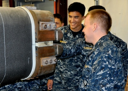 DAHLGREN, Va. (April 14, 2017) - U.S. Naval Academy Midshipmen peer down the barrel of the electromagnetic railgun prototype launcher at Naval Surface Warfare Center Dahlgren Division. Navy scientists and engineers briefed the Midshipmen on electromagnetic launchers, hypervelocity projectiles, and directed energy weapons, in addition to the command's capabilities in complex warfare systems development and integration to incorporate electric weapons technology into existing and future fighting forces and platforms.