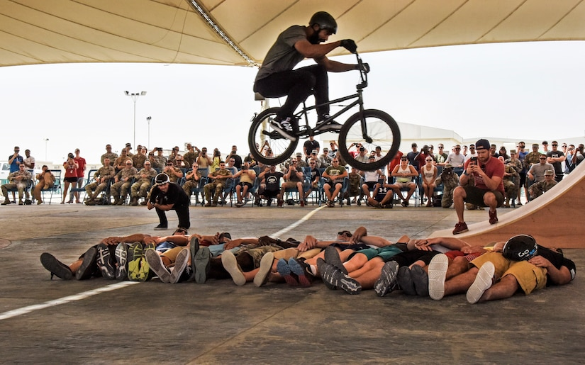 Mykel Larrin, a Bikes Over Baghdad BMX rider, jumps over service members at Al Udeid Air Base, Qatar, April 20, 2017. Bikes Over Baghdad is a professional team of BMX Riders who travel throughout the U.S. Central Command area of responsibility putting on shows for service members. (U.S. Air Force photo by Senior Airman Cynthia A Innocenti)