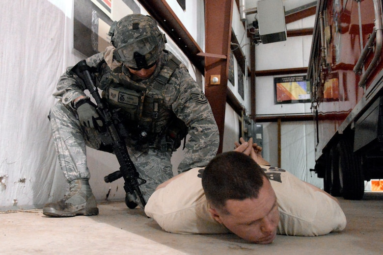 Tech. Sgt. Mark Hudson, 75th Security Forces Squadron, detains an Airman playing the role of an active shooter, Senior Airman David Andrews, 775th Civil Engineer Squadron, during a response exercise at Hill Air Force Base, April 24. (U.S. Air Force/Todd Cromar)