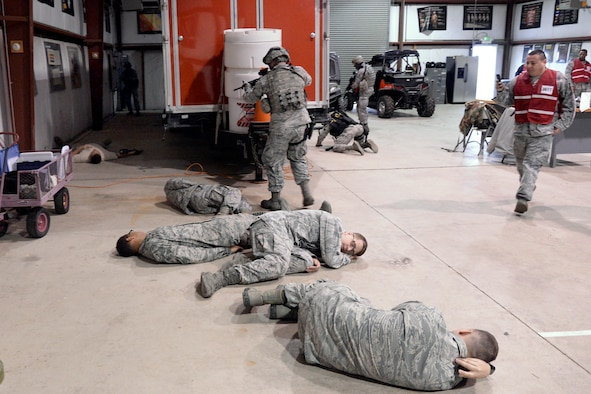 Airmen playing the role of hostages lay on the floor at building 732, Hill Air Force Base, while 75th Security Forces Squadron Airmen neutralize an Airman playing the role of an active shooter. Wing Inspection Team members in red vests look during the response exercise April 24. (U.S. Air Force/Todd Cromar)