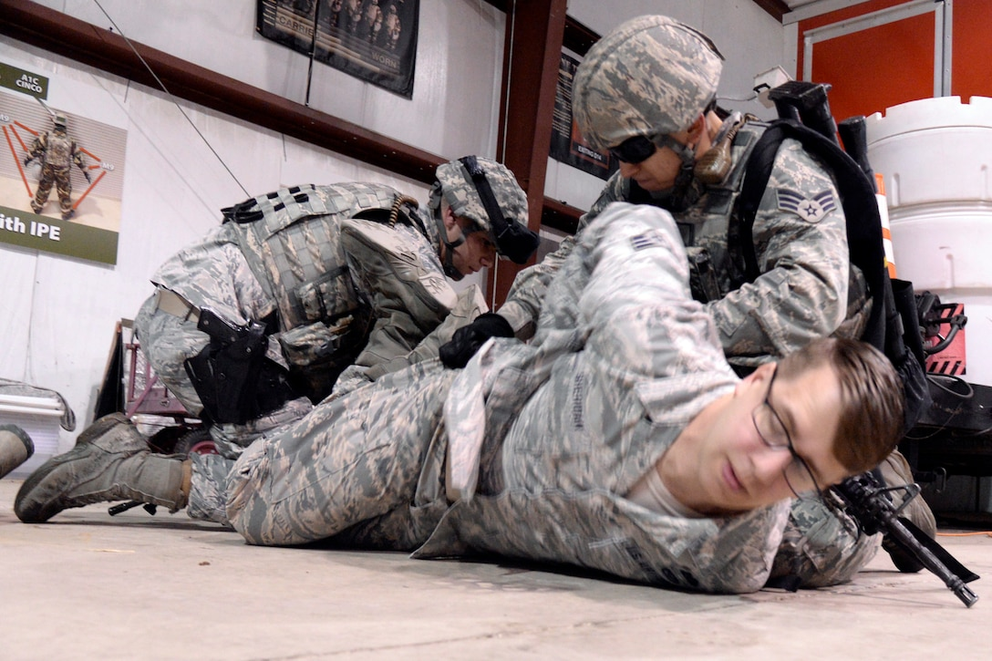 From the left, Airman 1st Class Glenn Jones and Staff Sgt. Deandre Brown, both 75th Security Forces Squadron, detain a role player, Senior Airman Alexander Sheridan, 775th Civil Engineer Squadron, during an active shooter response exercise April 24 at Hill Air Force Base. (U.S. Air Force/Todd Cromar)