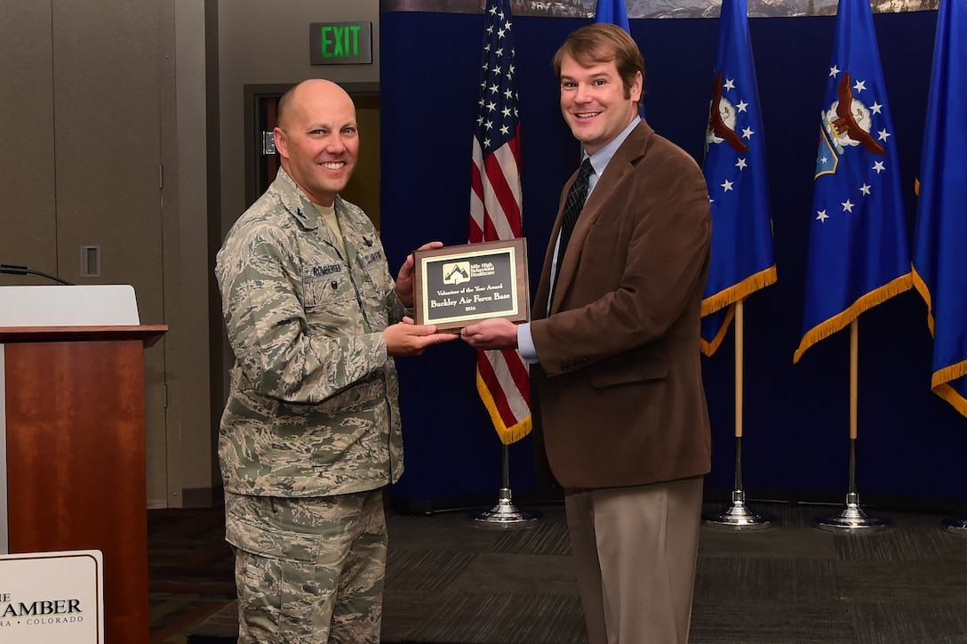 James Gillespie, director of development at Comitis Crisis Center, presents 460th Space Wing vice commander, Col. Scott Romberger, with the Volunteer of the Year Award on behalf of Buckley Air Force Base. Members of Team Buckley were cited for a collective contribution of over 350 hours to Comitis in 2016, including skilled and technical labor on capital improvement at the shelter. (U.S. Air Force photo by Airman 1st Class Jessica Huggins/released)
