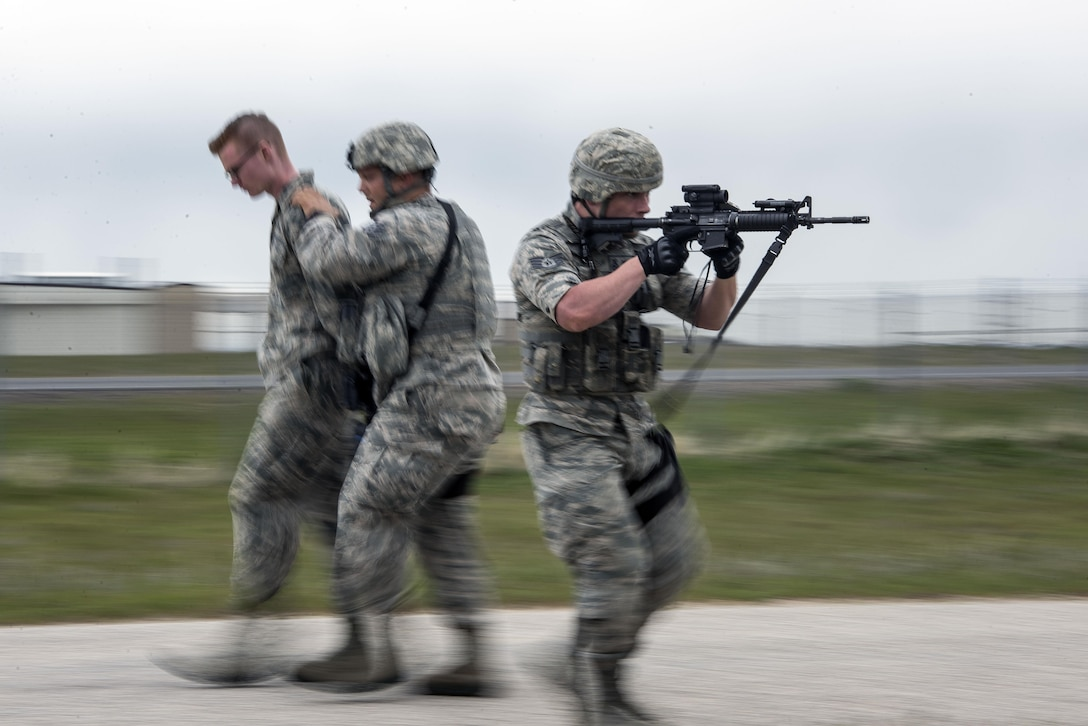 Staff Sgt. Jacob Sime, 75th Security Forces Squadron, provides cover while Staff Sgt. Jason Lyons, 75th SFS, removes Airman 1st Class Luke Litwaitis, 775th Civil Engineer Squadron, from the immediate vicinity of an active shooter during a response exercise at building 732, Hill Air Force Base, April 24. Liwaitis, who earlier 'escaped' and called police about an active shooter and explosives, was detained for questioning. (U.S. Air Force/Paul Holcomb)