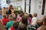 "DLA Distribution commander Army Brig. Gen. John S. Laskodi's wife Ursula reads ""There's a Lion in my Cornflakes"" to one of the classrooms at the Defense Distribution Center Susquehanna Child Development Center, in honor of Month of the Military Child on April 19."